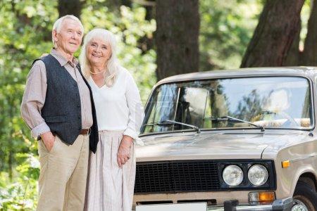 senior man and woman standing near beige car