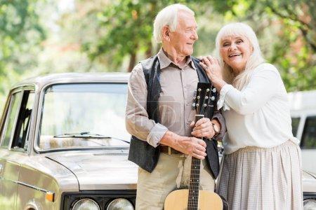 senior woman embracing man with guitar against beige vintage car