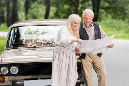 senior husband and wife holding map and leaning on car