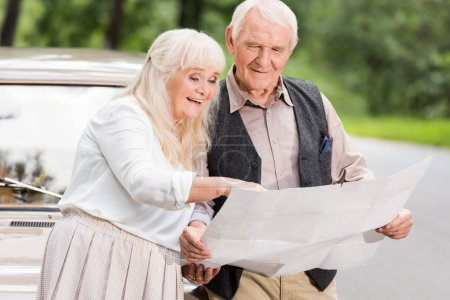 happy senior couple holding map and leaning on retro car