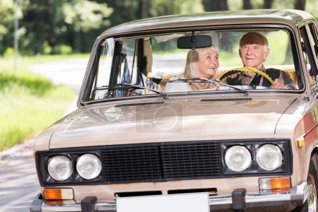 happy senior couple driving retro car