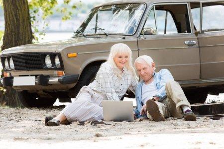 Happy senior couple sitting on sand and using laptop near beige vintage car