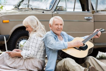 senior wife using laptop while husband playing guitar against beige vintage car