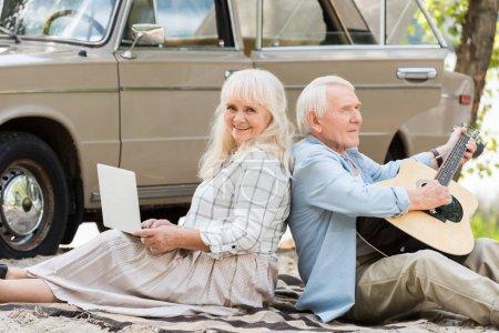 senior woman using laptop while man playing guitar against vintage car