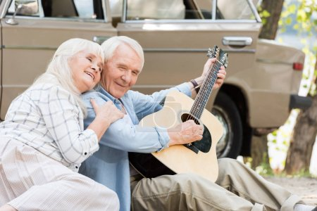 senior woman sitting on sand with man playing guitar against vintage car