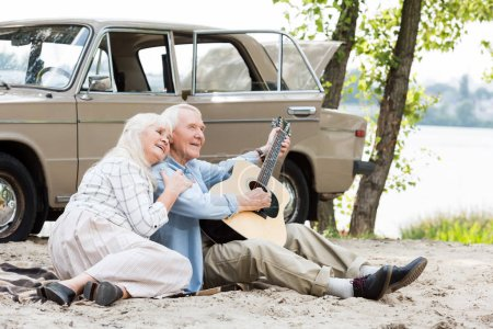beautiful senior woman sitting on sand with man playing guitar against beige vintage car