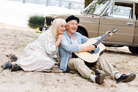 smiling senior woman sitting on sand with man playing guitar against beige car
