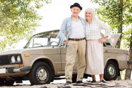 Photo pour Vue de dessous du couple de personnes âgées debout près d'une voiture vintage beige et regardant la caméra - image libre de droit