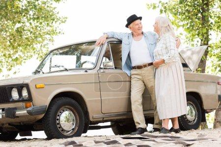 Photo pour Vue de dessous d'élégant couple senior debout près d'une voiture vintage beige et regardant les uns les autres - image libre de droit