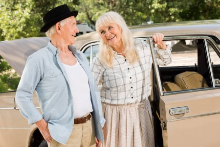Photo for Beautiful senior couple standing near beige car and looking at each other - Royalty Free Image