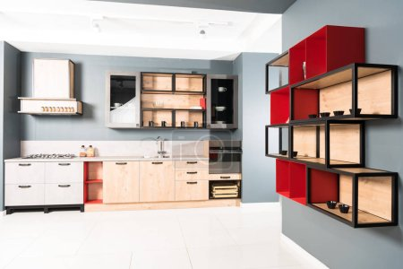 interior of modern clean light kitchen with furniture and wooden red shelves