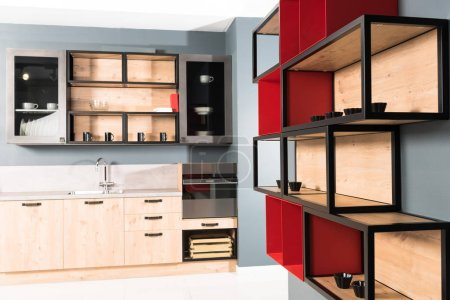 Photo for Interior of modern clean light kitchen with kitchen counters and red shelves - Royalty Free Image