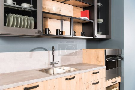 Photo for Part of modern clean light kitchen with sink, tap and shelves with plates - Royalty Free Image