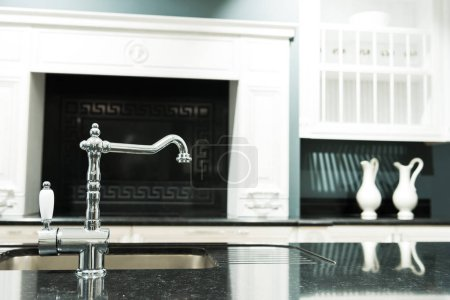 part of modern kitchen in baroque style with tap and sink