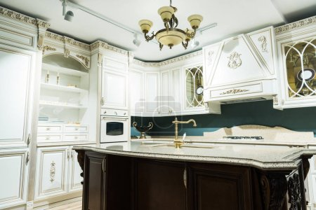 interior of modern white kitchen with comfortable wooden furniture in baroque style