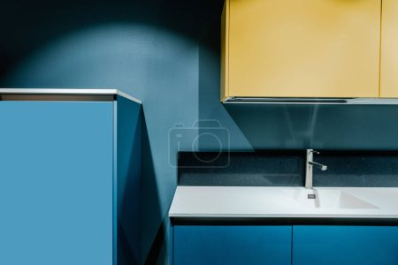 part of contemporary kitchen with blue and yellow shelves and tap