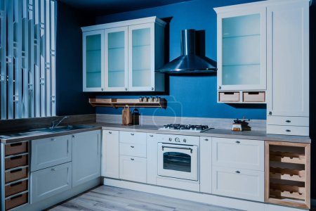 interior of contemporary wooden kitchen with white furniture and blue walls