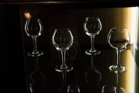 different glasses on shelf in kitchen with dark light