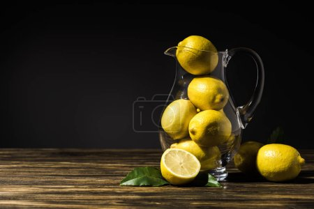 glass jug with yellow lemons on wooden tabletop
