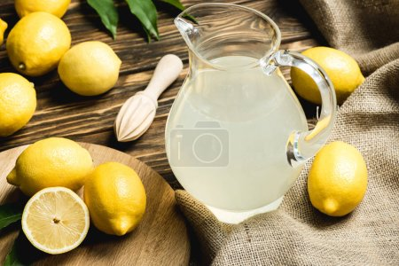 glass jug with fresh juice, squeezer and yellow lemons on sacking on wooden surface