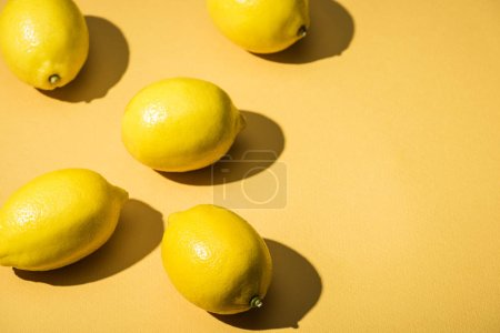 fresh lemons on yellow minimalistic background with copy space