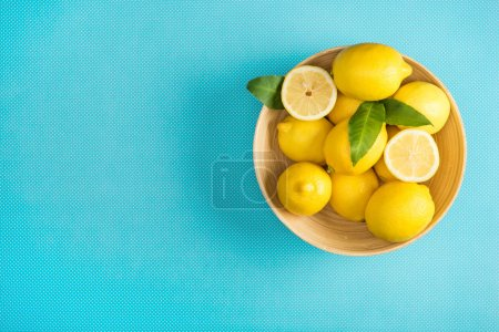 top view of fresh lemons with leaves in wooden plate on turquoise background