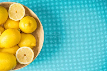 Top view of yellow lemons in wooden plate on turquoise background with copy space
