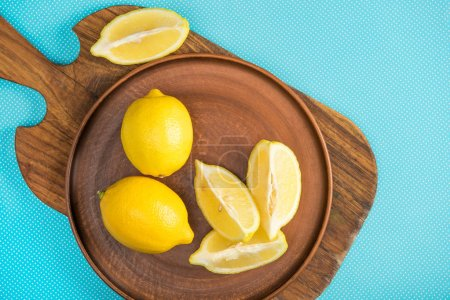 Photo for Top view of yellow lemons in ceramic plate on wooden cutting board on turquoise - Royalty Free Image