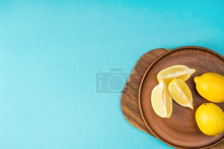 top view of lemons in ceramic plate on wooden board on turquoise with copy space