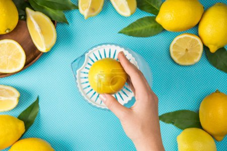 Photo for Top view of female hand with lemons and squeezer on turquoise background - Royalty Free Image