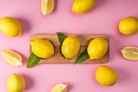 top view of fresh yellow lemons on wooden board on pink background