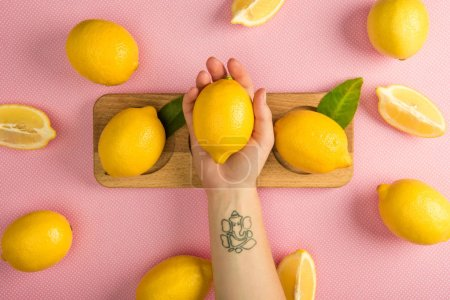 cropped view of woman holding yellow lemon over pink table with juicy lemons