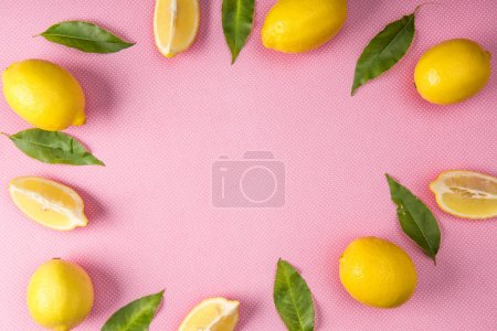 top view of frame made from yellow lemons and leaves on pink background with copy space