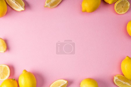 top view of frame made from fresh yellow lemons on pink background