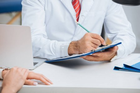 Photo for Partial view of physiotherapist in white coat making notes in notepad with female patient near by during appointment in clinic - Royalty Free Image
