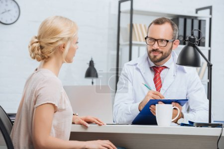 Photo pour Chiropratique en manteau blanc prenant des notes dans un bloc-notes avec une patiente près de la table pendant le rendez-vous à la clinique - image libre de droit