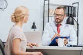 chiropratique en blouse blanche, prendre des notes dans le bloc-notes avec patiente près d'à table lors de rendez-vous en clinique