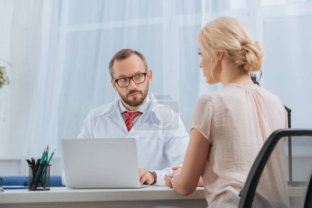Photo for Physiotherapist in white coat having conversation with female patient at workplace with laptop in hospital - Royalty Free Image