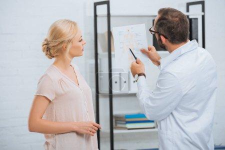 Photo pour Chiropratique en manteau blanc montrant schéma du corps humain au patient féminin à l'hôpital - image libre de droit