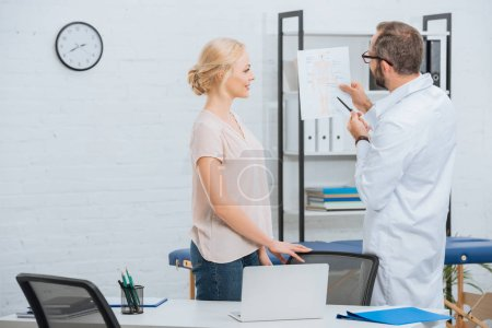 Photo pour Chiropratique au régime de corps humain montrant blouse blanche à la patiente à l'hôpital - image libre de droit