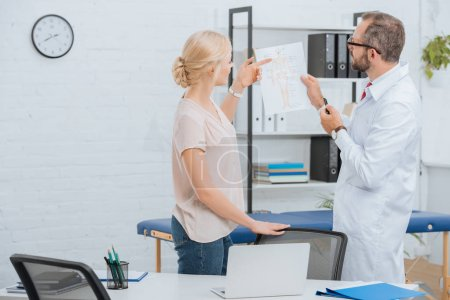 chiropractic in white coat showing human body scheme to female patient in hospital
