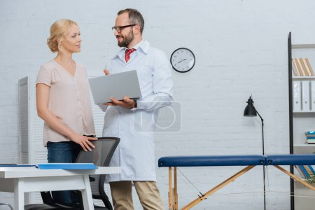 Photo for Physiotherapist in white coat with laptop and female patient looking at each other in hospital - Royalty Free Image