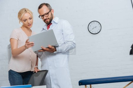 Photo for Portrait of chiropractor in white coat and female patient using laptop in hospital - Royalty Free Image
