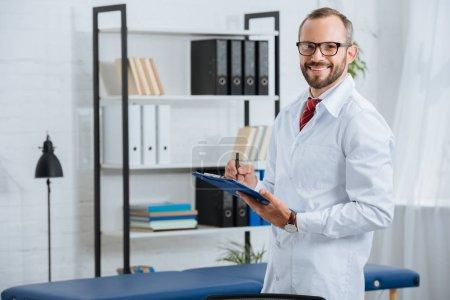 Photo pour Portrait de chiropraticien masculin souriant en manteau blanc et lunettes avec bloc-notes à l'hôpital - image libre de droit