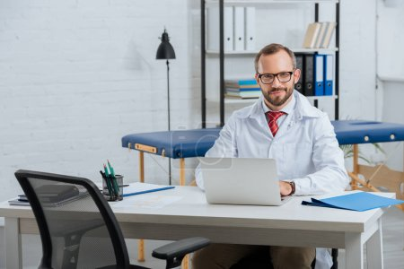 portrait of smiling male chiropractor in white coat at workplace with laptop in hospital