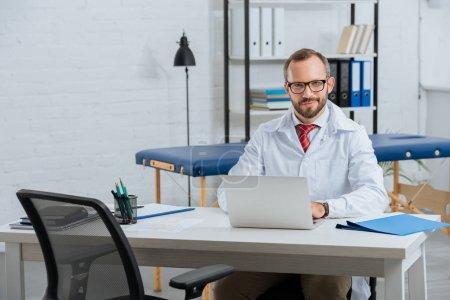 Photo pour Portrait de sourire masculin chiropraticien en blouse blanche au milieu de travail avec ordinateur portable à l'hôpital - image libre de droit