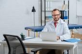 Portrait de sourire masculin chiropraticien en blouse blanche au milieu de travail avec ordinateur portable à l'hôpital