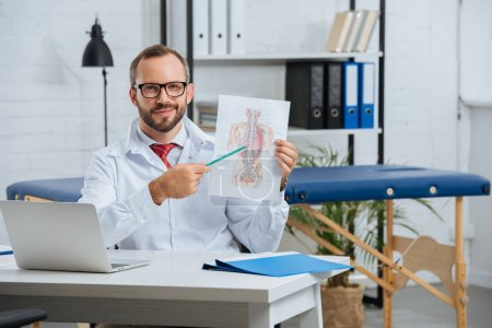 Photo for Portrait of male chiropractor in white coat and eyeglasses pointing at human body scheme in hospital - Royalty Free Image