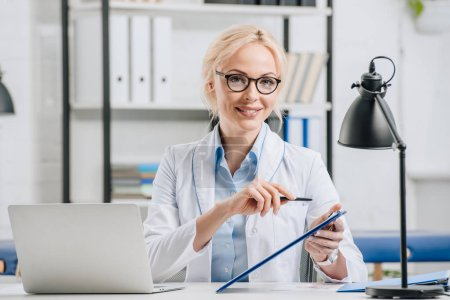 portrait of smiling chiropractor in eyeglasses and white coat pointing at notepad at workplace in clinic
