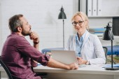 patient having appointment with smiling physiotherapist in hospital